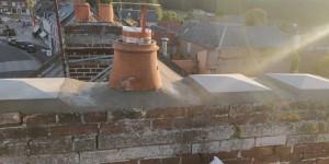 Photo de galerie - Rénovation d'une souche de cheminée endommagée. Supression de 3 poterie sur 4 et condamnation. Répartition dernière poterie et tubage du dernier conduit. APRÈS.